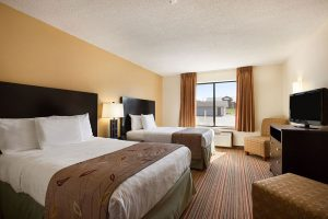 Two queen beds across from TV and dresser at Ramada by Wyndham Wisconsin Dells