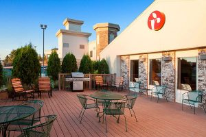 Outdoor patio with BBQ grill, tables, and chairs at Ramada by Wyndham Wisconsin Dells